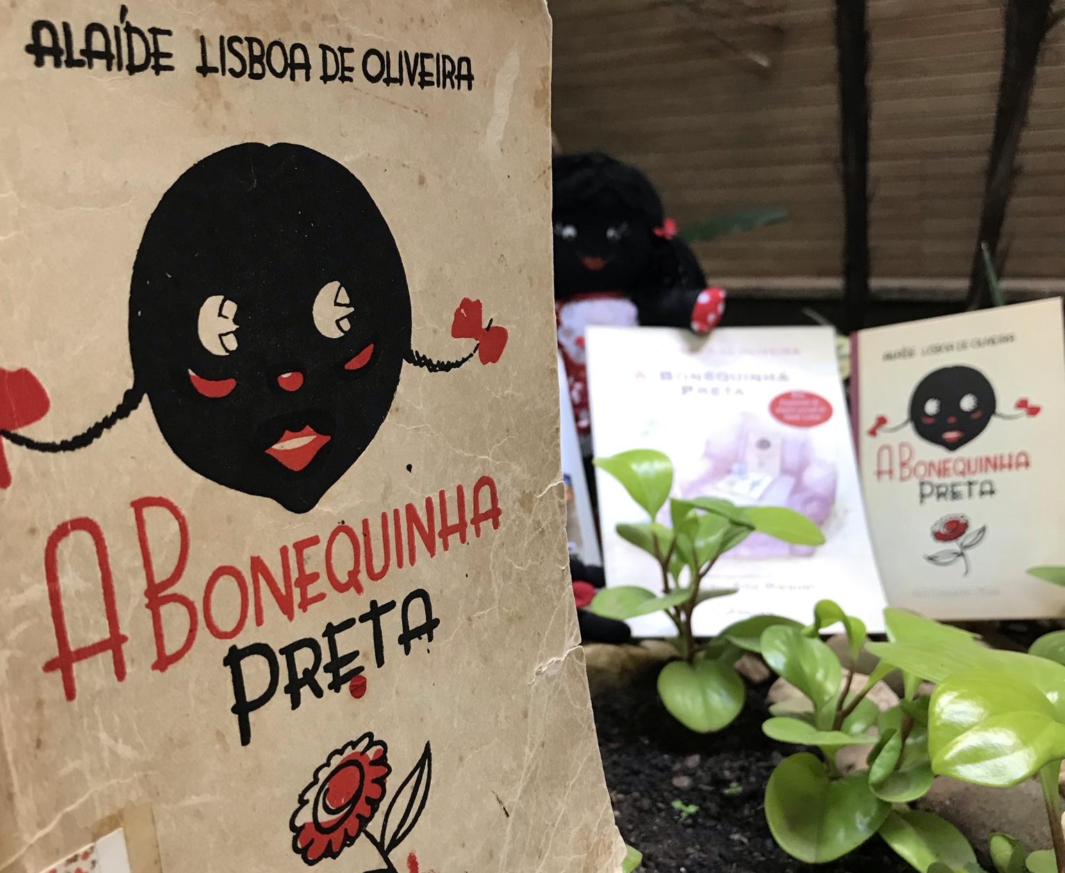 Livro A Bonequinha Preta clássico, com outras versões ao fundo.