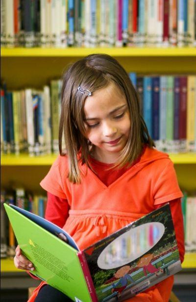 Menina lendo na biblioteca. Imagem ilustrativa texto nota no Ideb.