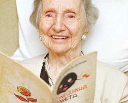 Autora Alaíde Lisboa de Oliveira com o livro A Bonequinha Preta original.