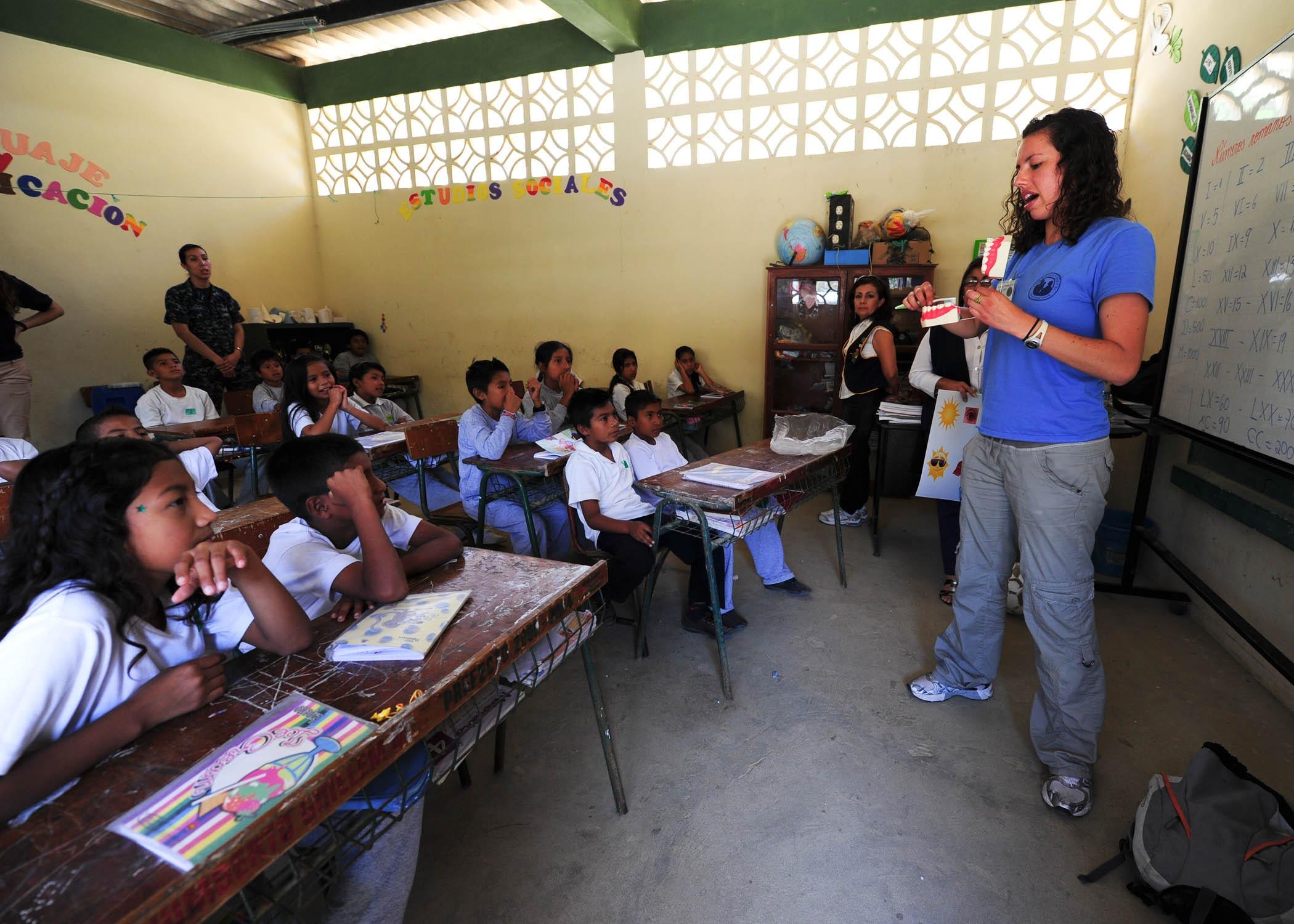 Mulher falando para crianças em sala de aula. Imagem ilustrativa texto Dia do Pedagogo.