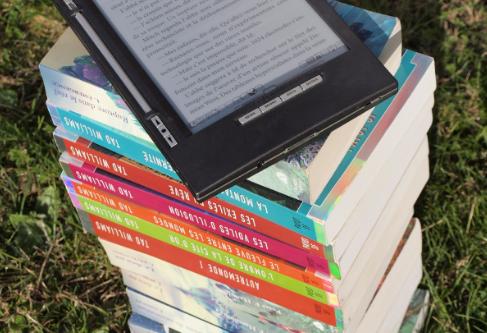 e-reader em cima de livros empilhados. Imagem ilustrativa texto livro físico.