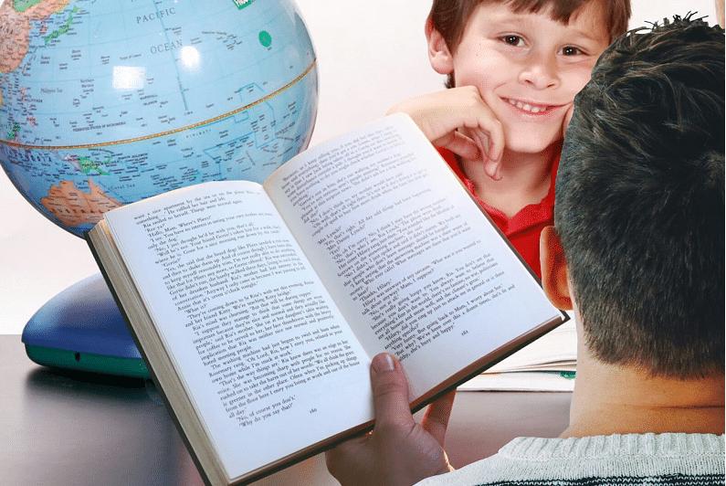 Menino de frente para adulto com livro na mão, com globo terrestre na mesa. Imagem ilustrativa texto biblioterapia.