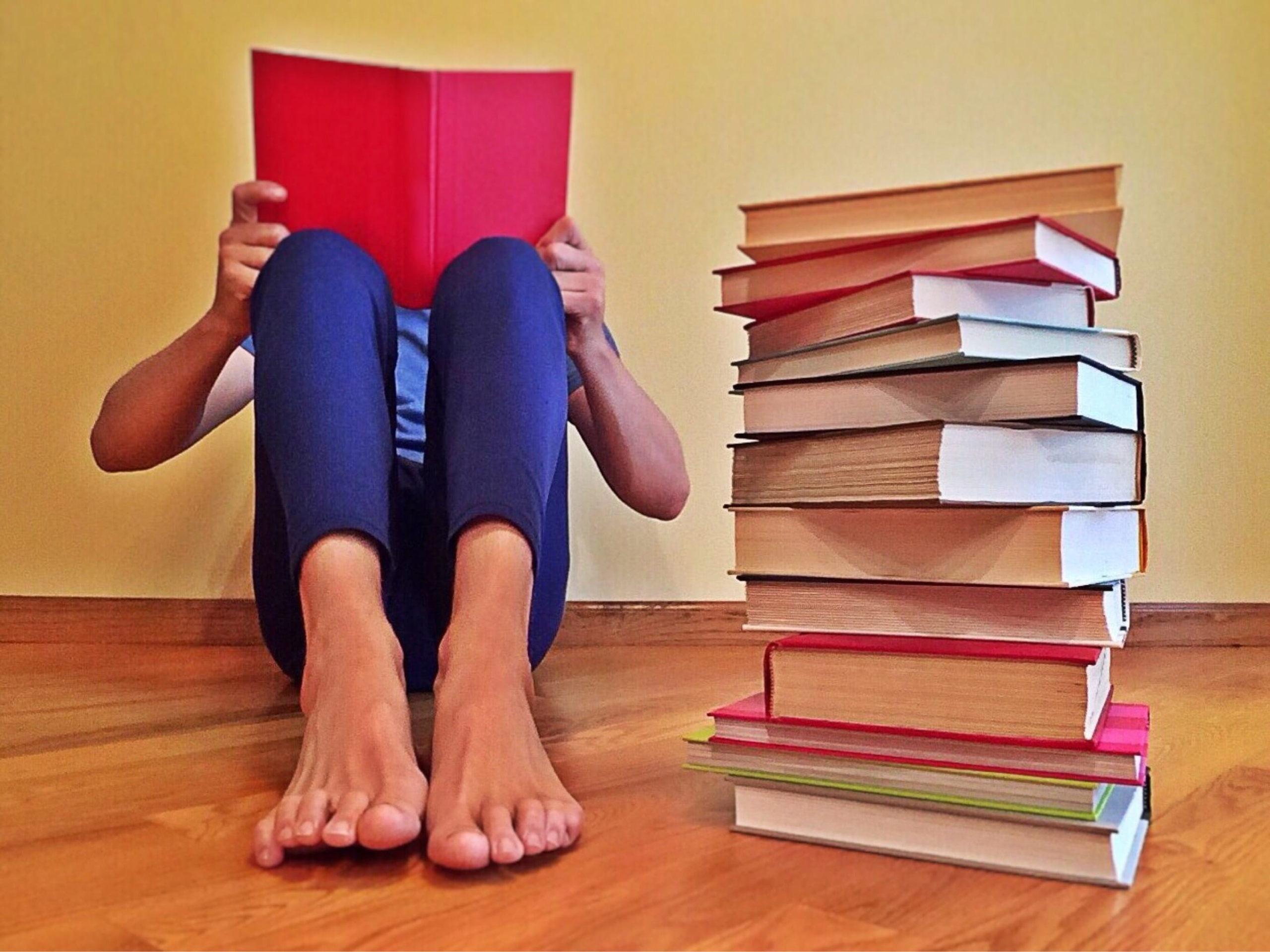 Criança lendo sentada no chão, ao lado de uma pilha de livros. Imagem ilustrativa texto cheiro de livro.