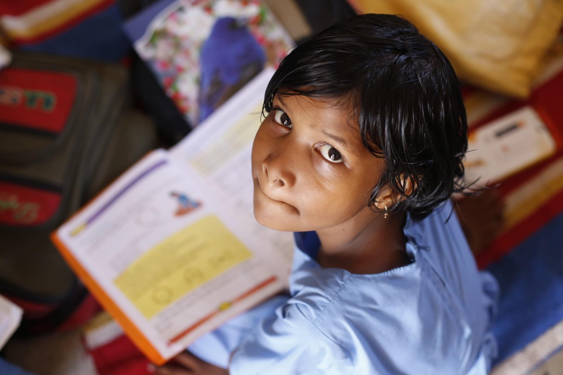 Menina olhando para a câmera, com livro na mesa. Imagem ilustrativa texto biblioterapia.
