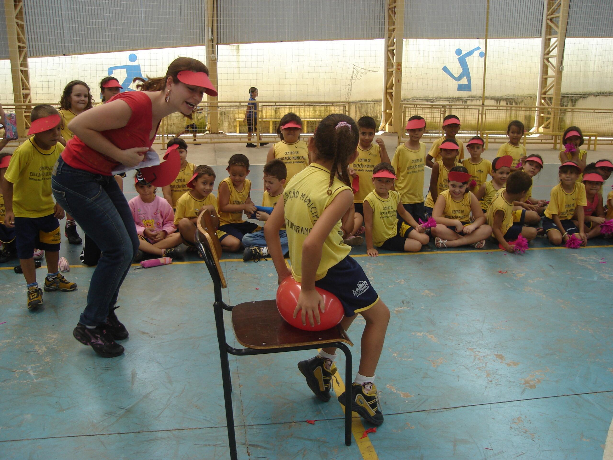 Competição de estourar balão na escola. Imagem ilustrativa texto importância da Educação Física.