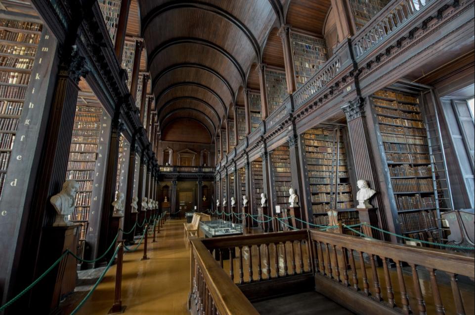 Corredor com arcos de madeira escurada biblioteca da Trinity College. Imagem ilustrativa texto bibliotecas mais bonitas do mundo.