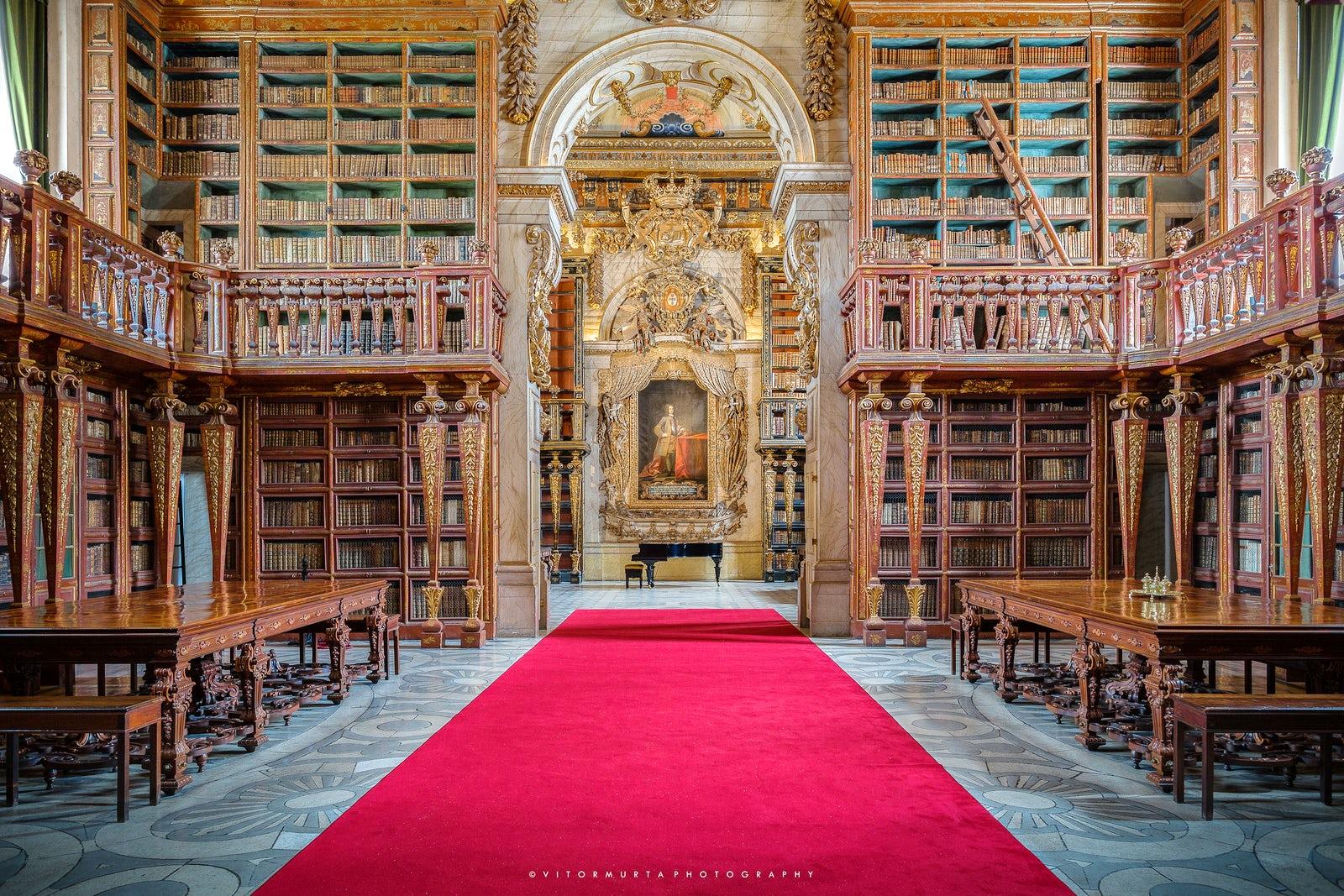 Interior da Biblioteca Joanina, com piano de cauda e pintura ao fundo, Universidade de Coimbra. Imagem ilustrativa texto bibliotecas mais bonitas do mundo.