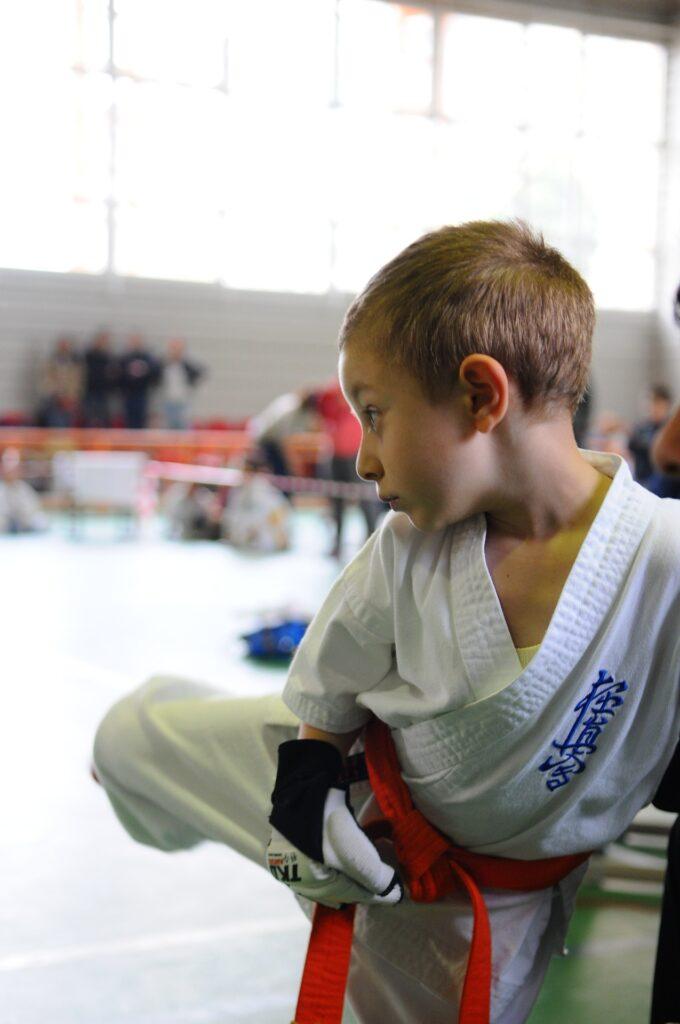 Menino de quimono, praticando artes marciais. Imagem ilustrativa texto iniciar as crianças nos esportes.