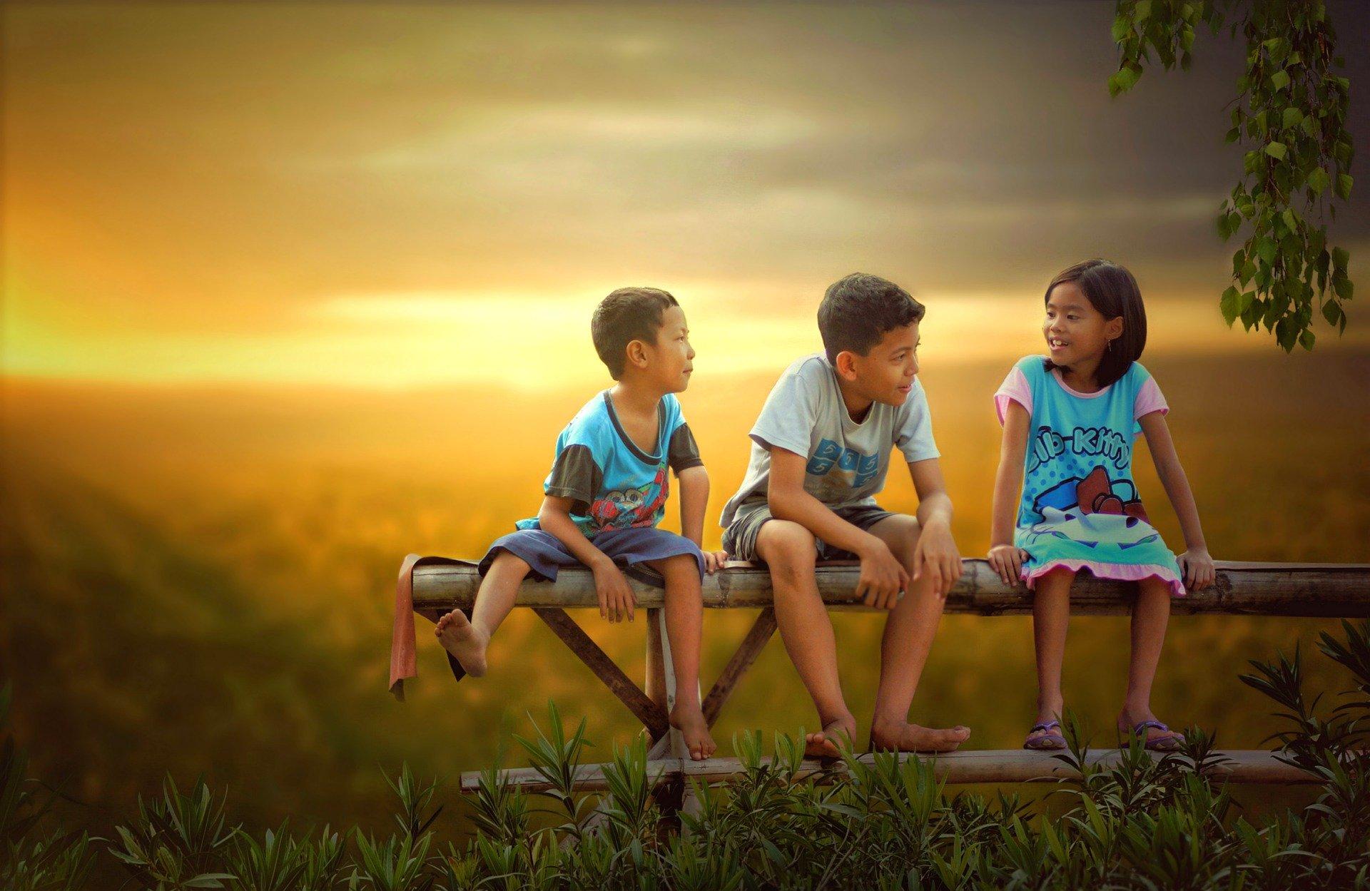 Dois meninos e uma menina sentados do banco, conversando, ao pôr do sol. Imagem ilustrativa texto brincadeiras com as palavras.