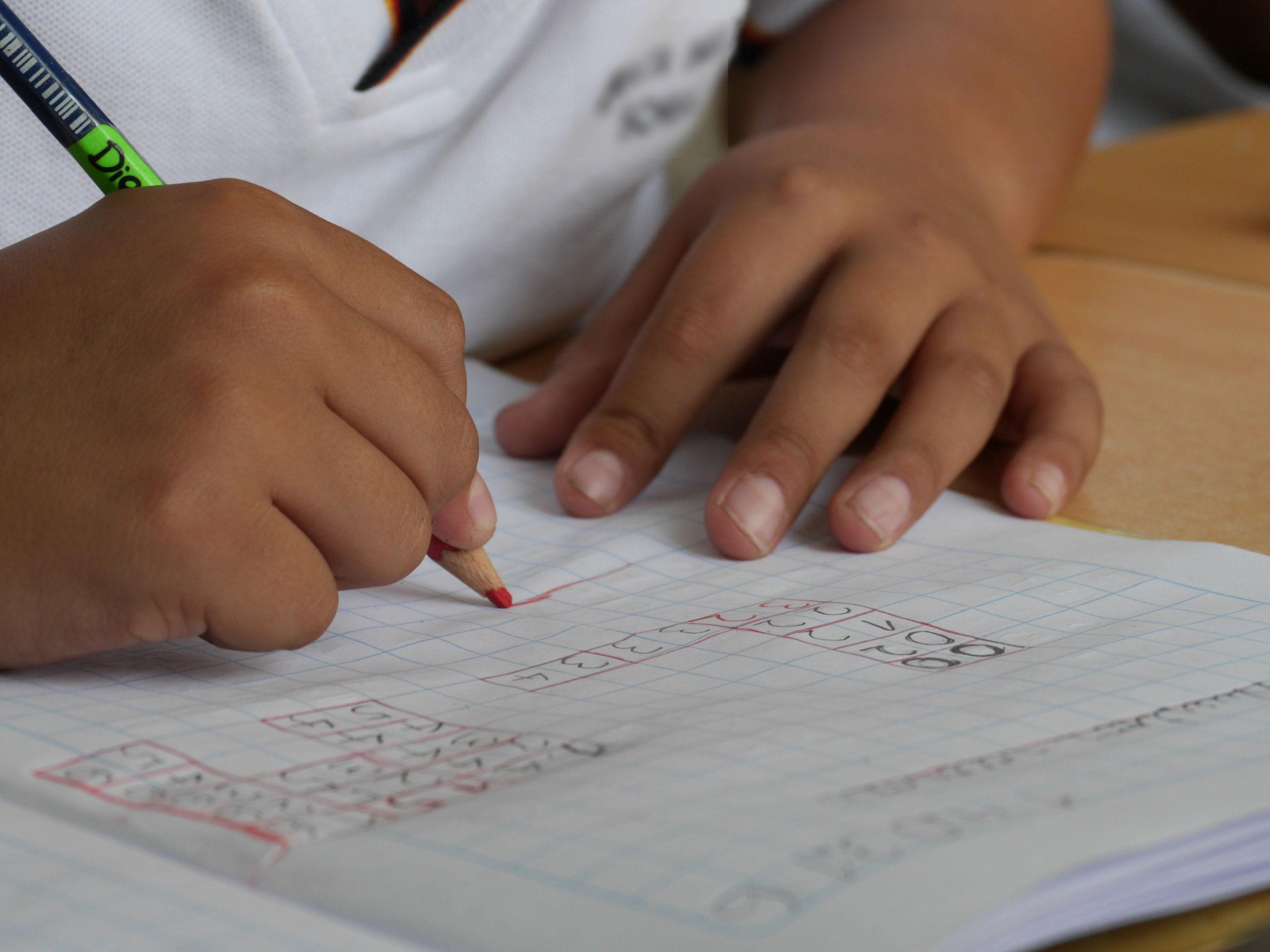Mãos de criança com lápis vermelho no caderno. Imagem ilustrativa texto dia do Estudante.