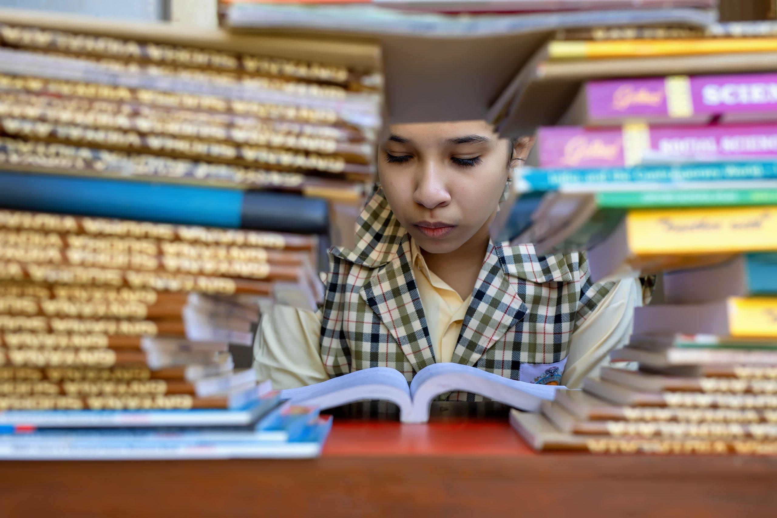 Menina lendo, atrás dos livros. Imagem ilustrativa texto nota no Ideb.