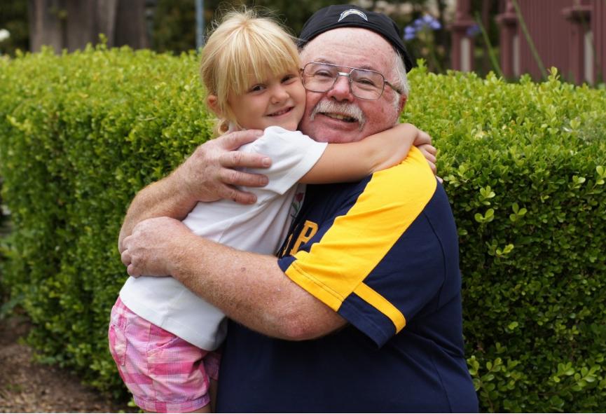 Neta abraçando avô. Imagem ilustrativa texto Dia dos Avós.