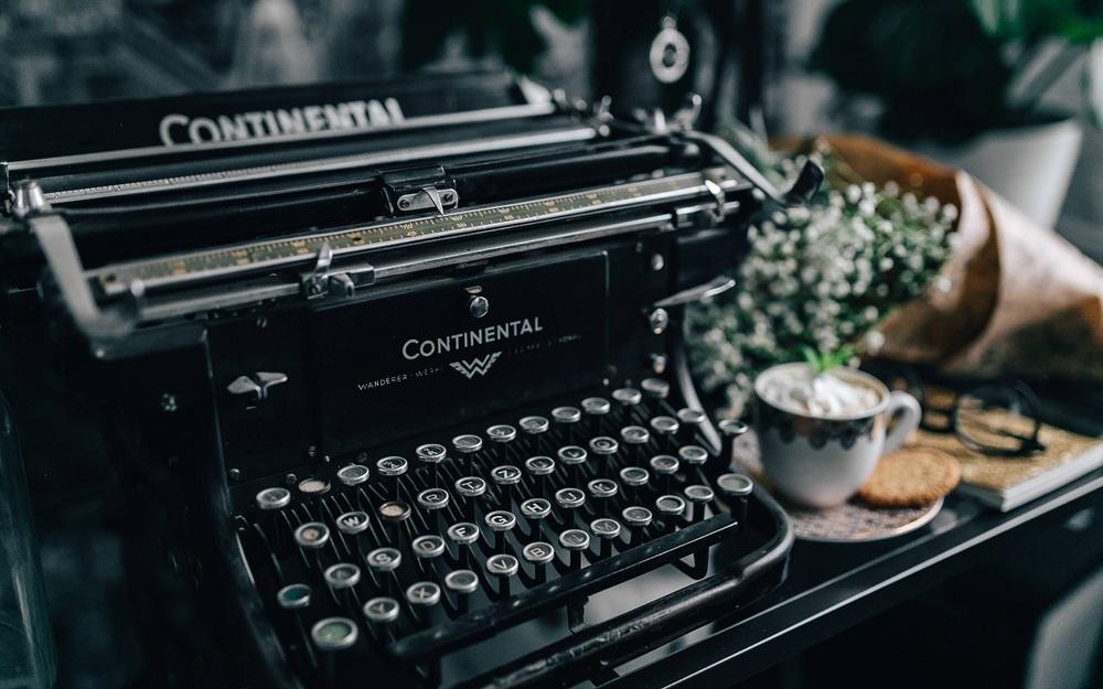 Máquina de escrever, com flores e café Imagem ilustrativa texto escritores.