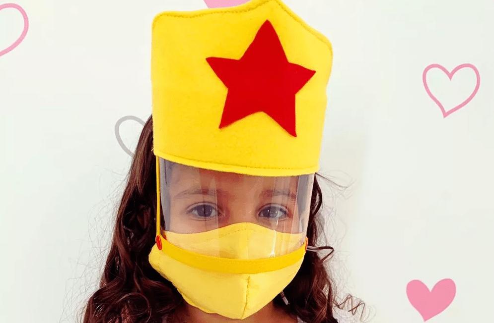 Menina usando máscara de proteção infantil customizada. Imagem ilustrativa texto customizar máscara infantil.