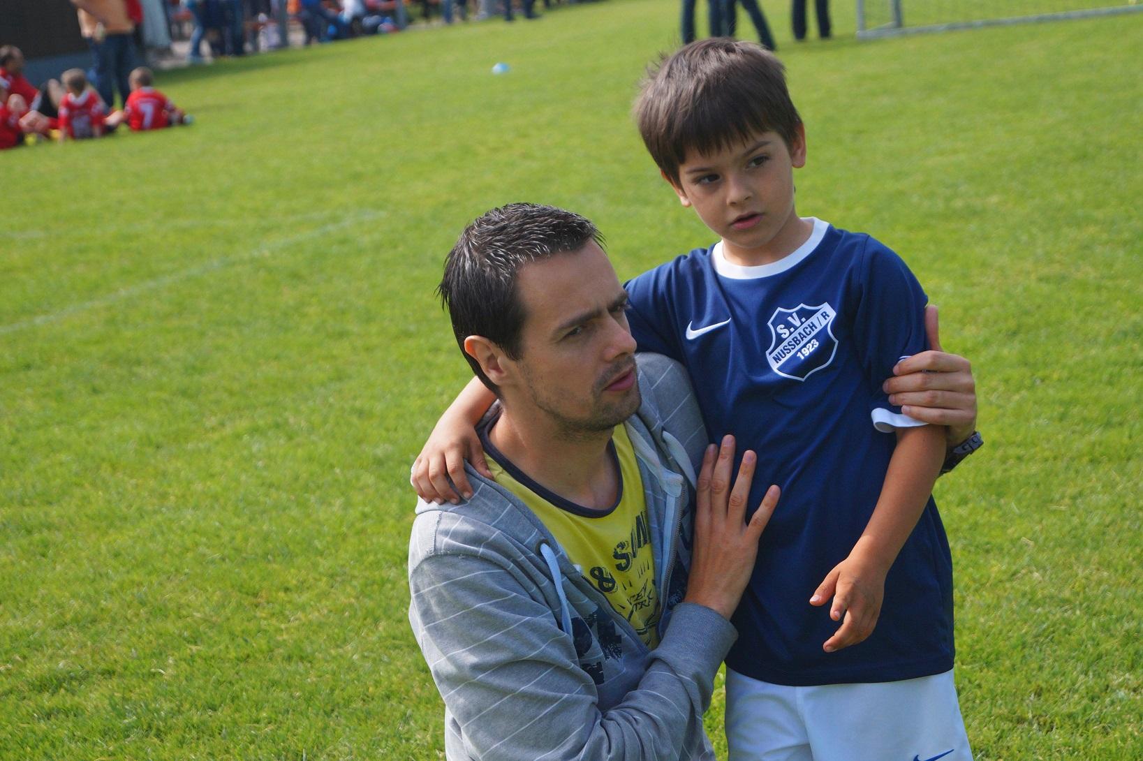 Pai com menino no campo de futebol. Imagem ilustrativa texto iniciar as crianças nos esportes.